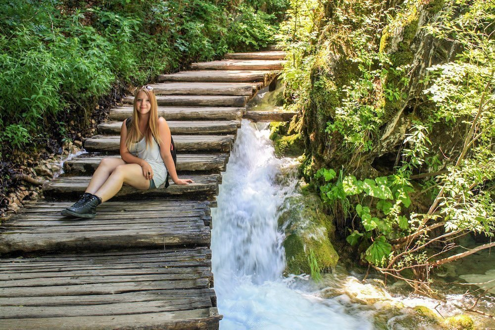 Taylor sits on a wooden boardwalk over a waterfall in Plitvice National Park, Croatia
