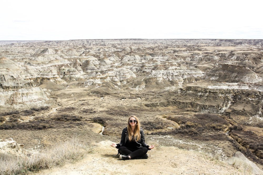 Taylor sits in a meditation pose above the dusty canyon at Dinosaur Provincial Park in Alberta, Canada