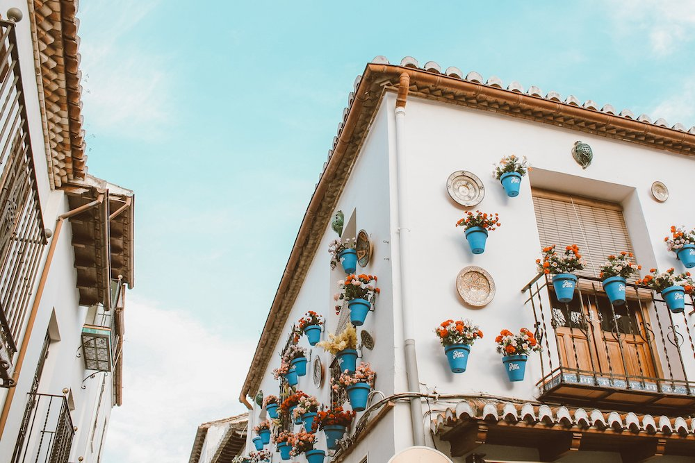A white, terracotta roofed house with plants hanging outside in the Albaicin of Granada Spain