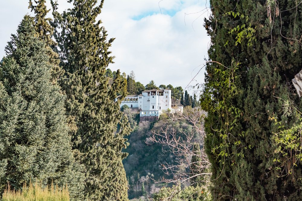 A white building stands among tall trees in Granada, Spain