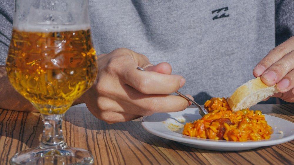 A person eats a tapa and drinks a beer in Granada, Spain