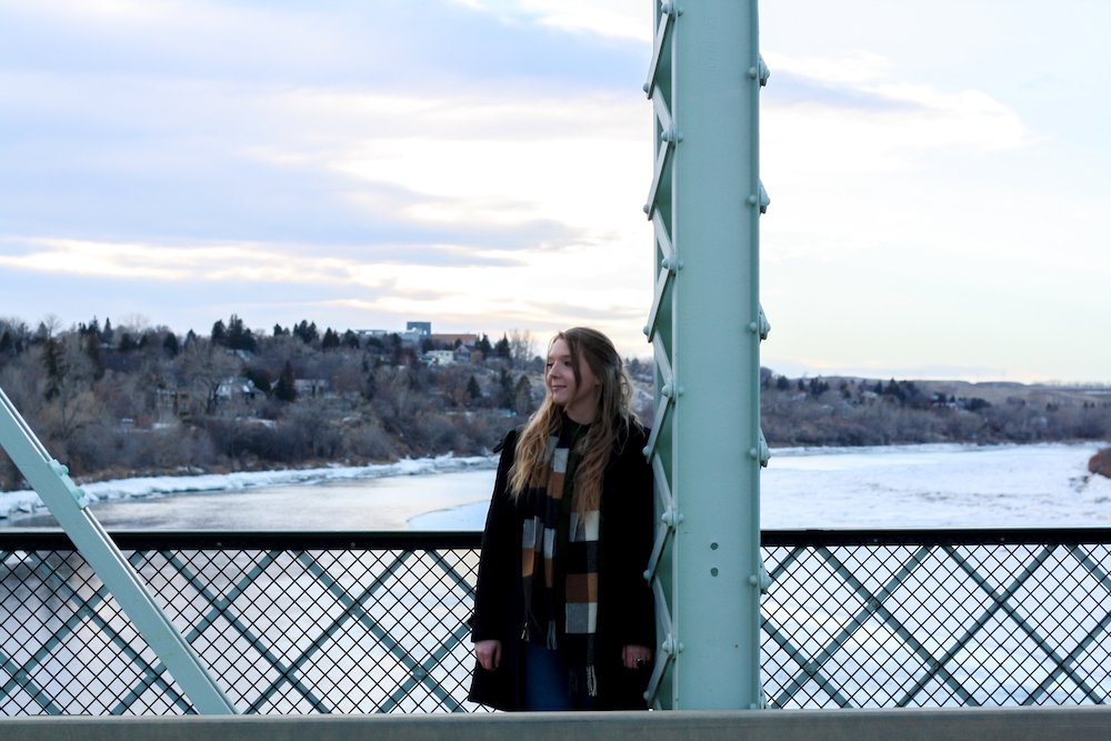 Taylor stands on a bridge near a beam in Medicine Hat, Canada in the winter