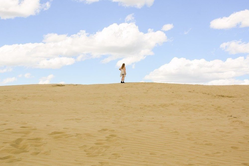 Taylor stands on the horizon line at the Great Sandhills of Saskatchewan on a cloudy day