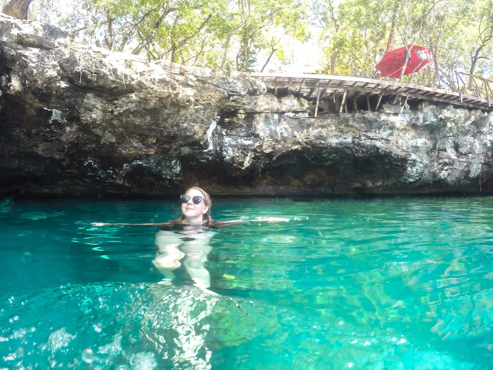 Taylor swims in a turquoise cenote near Playa del Carmen, Mexico