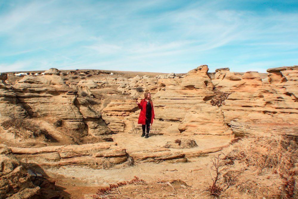 Taylor stands amongst red rock hoodoos in Writing-on-stone provincial park in Alberta