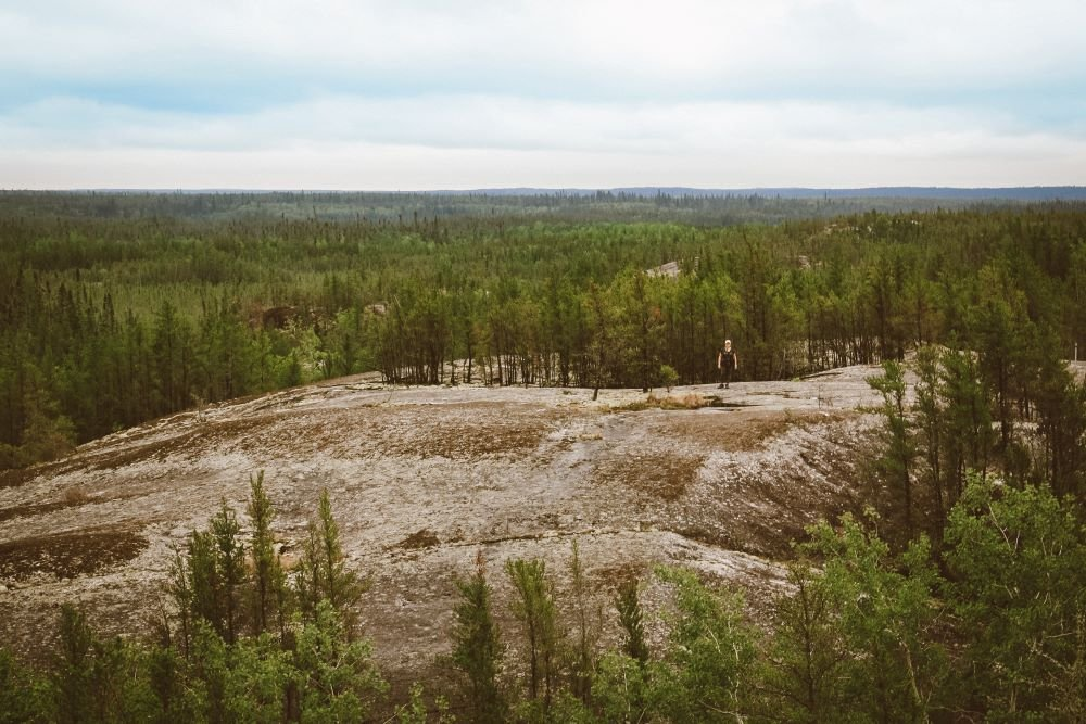 Rita stands on a rock surrounded by precambrian shield and green trees in Nopiming Provincial Park, Manitoba