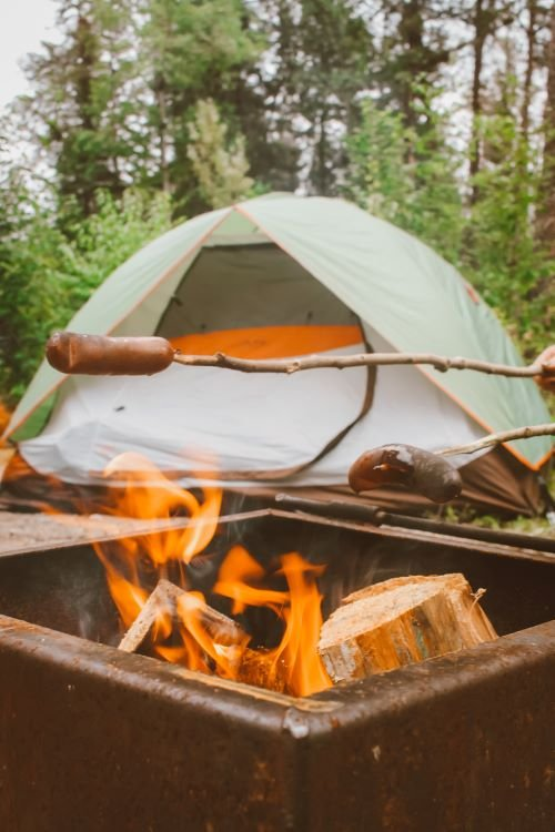 Two sausages cook over a fire with a tent in the background at Nopiming Provincial Park, Manitoba