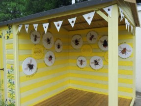 A yellow cubby house with pictures of bees