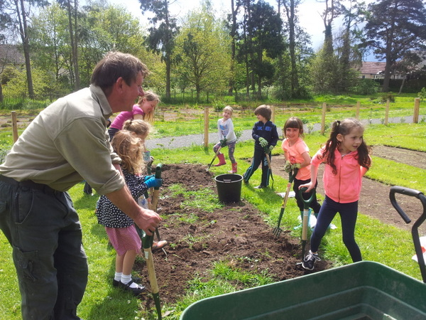Gardener telling children how to dig