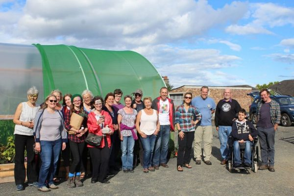 A photo of a group of volunteers in front of the polytunnel