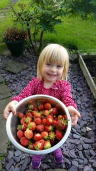 A photo of Nina with home grown strawberries