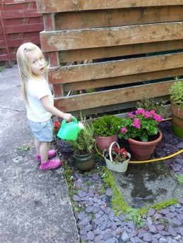 A photo of Nina watering the flowers