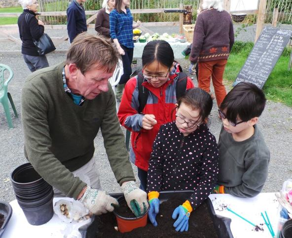 A photo of Peter demonstrating bulb planting