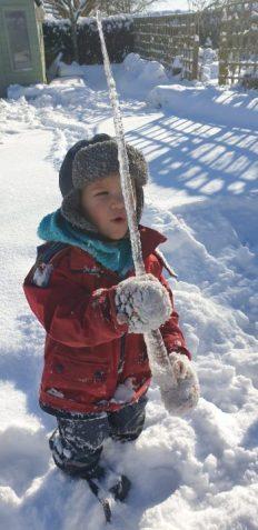Photo of child holding a large icicle