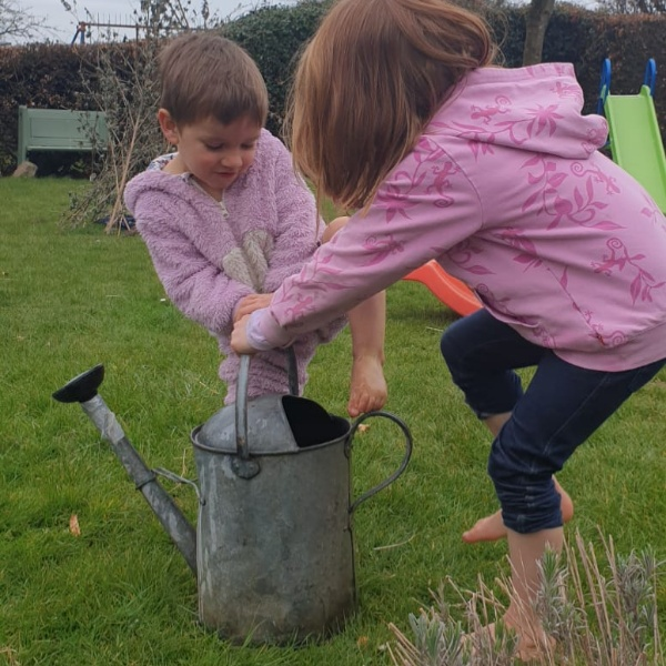 A photo of kids playing with a watering can