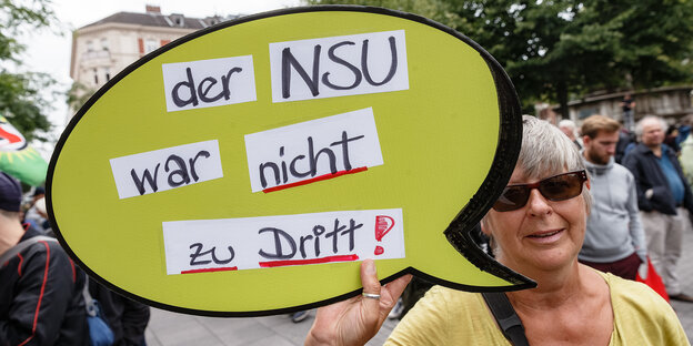 A protester holds a sign with the inscription