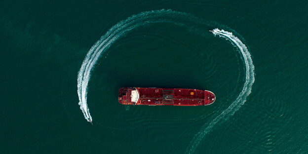a large ship is circled by two speedboats