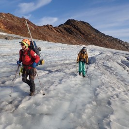Researchers/field assistants hike to recover a seismic station
