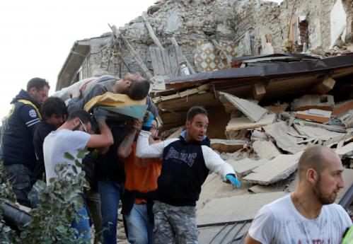 A man is carried away after having been rescued alive from the ruins following an earthquake in Amatrice, central Italy, August 24, 2016. REUTERS/Remo Casilli