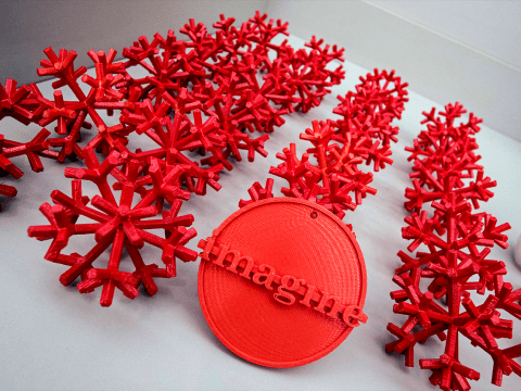 Red 3D printed snowflake ornaments and one circular ornament that reads 'imagine'