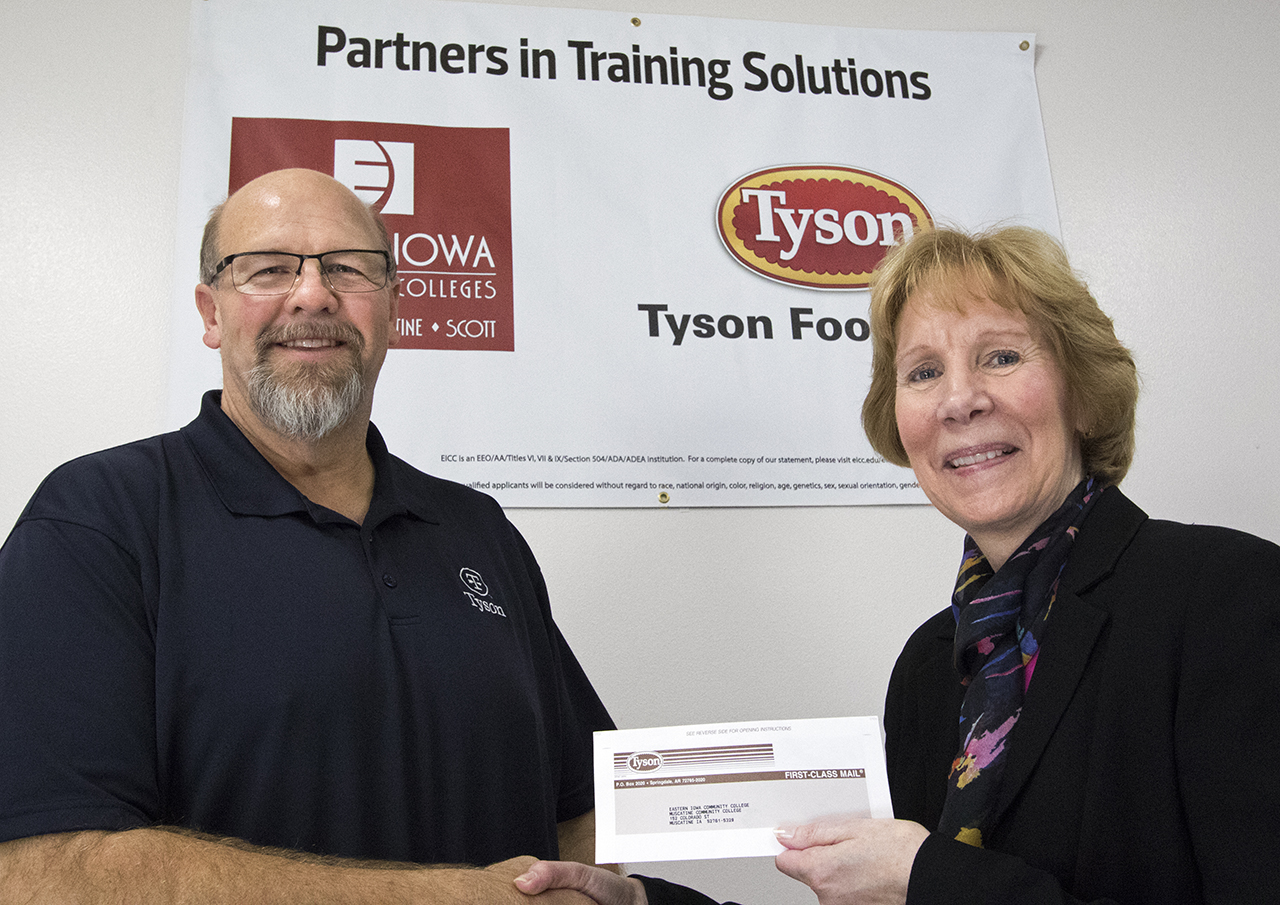 Tyson Foods Human Resources Director Dave Duncan presents Eastern Iowa Community Colleges (EICC) Dean of Continuing Education Deb Goodall with a check for $15,000.