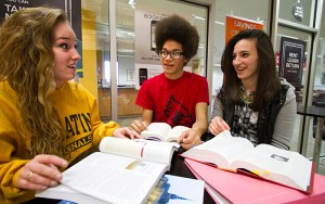 Three diverse students sitting at table with textbooks talking