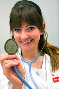Female student holding up stethoscope