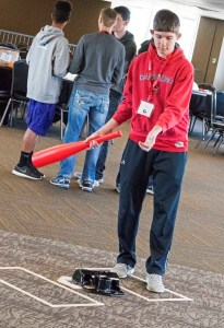 Student hitting ball with baseball bat