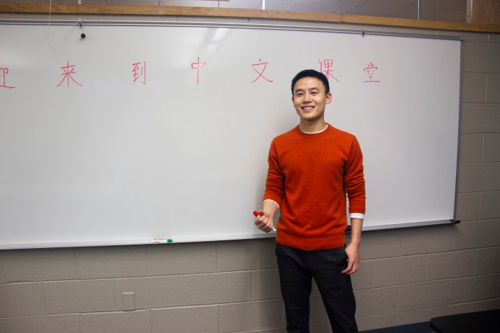 Manadrin instructor standing in front of white board with mandarin characters written on it