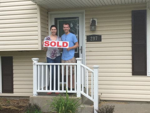 Couple holding sold sign in front of their new home