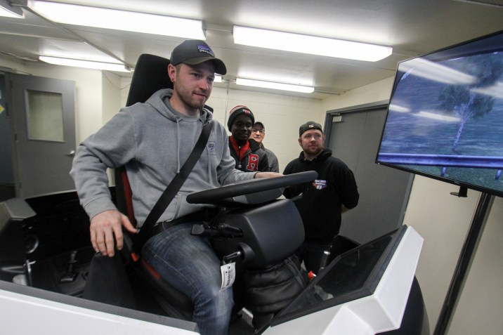 Student driving on the truck simulator with other students watching