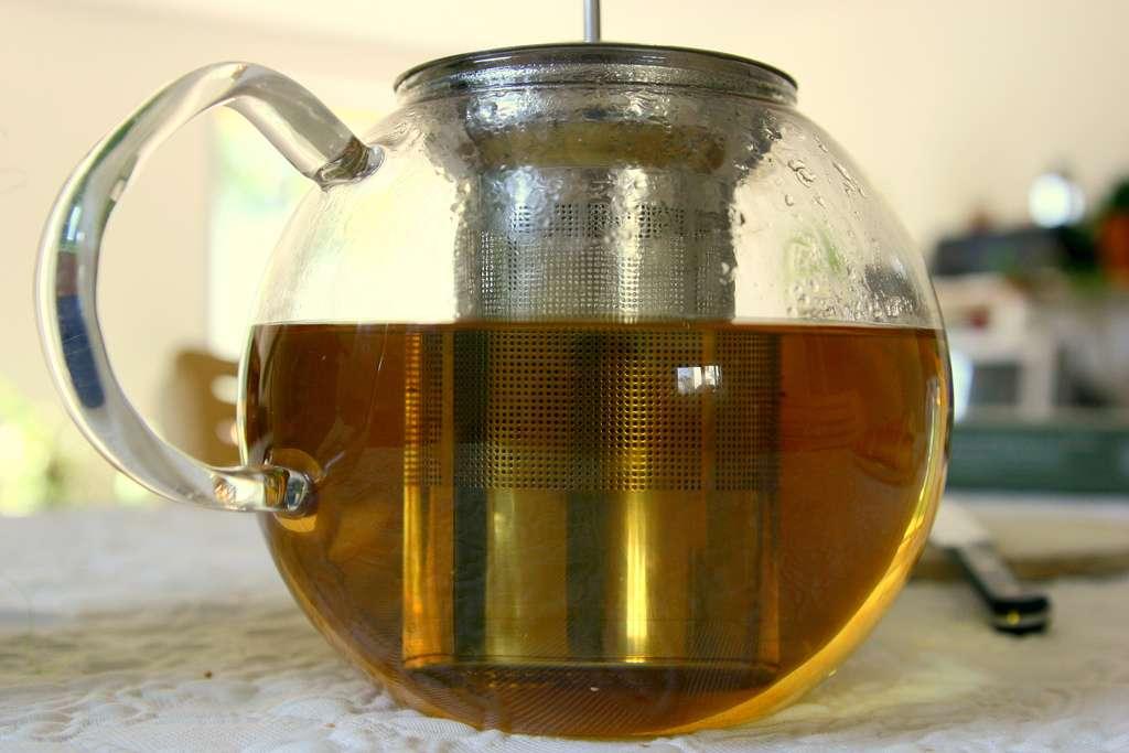 Darjeeling tea in a metal diffuser in a glass teapot