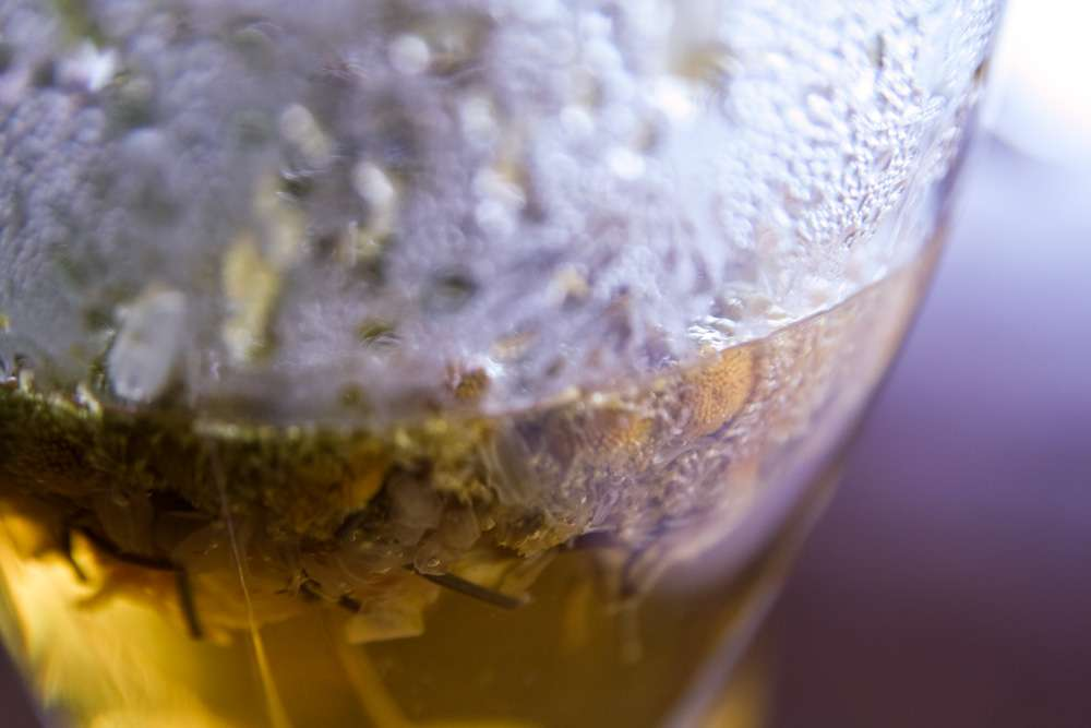 Close-up photo of tea steeping in a clear glass with condensation and steam
