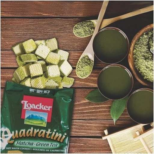 Photo of Loacker Quadratini Premium Matcha Green Tea Wafer Cookies spilling out of the package onto a wooden surface next to spoons of matcha powder and cups of green tea.