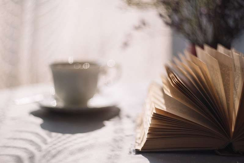 Photo of a book fanned open in the foreground and a cup of tea steaming in the background.