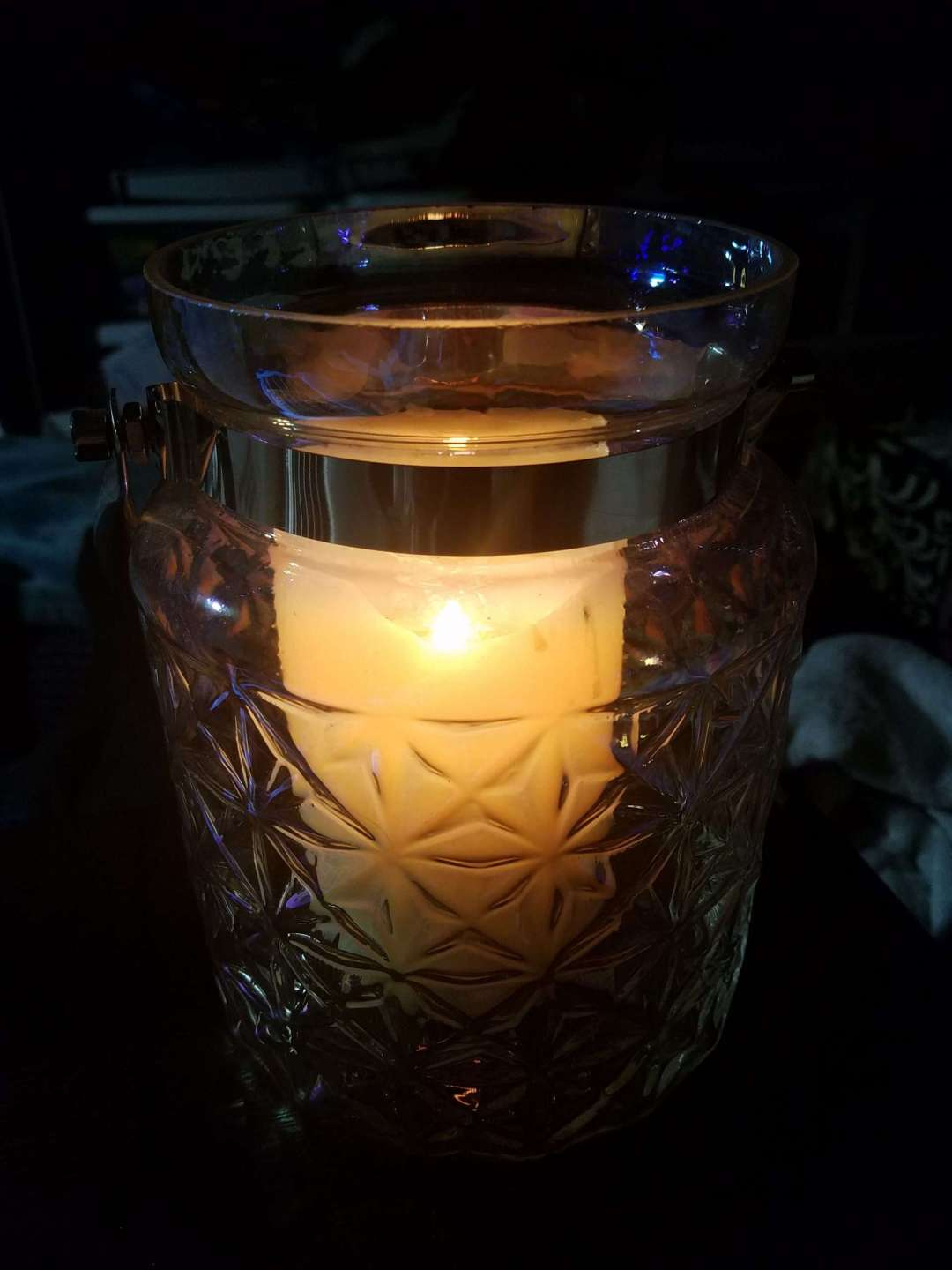 Solstice Night, Tea, and Light - Photo of a lit candle in a glass jar illuminating the darkness