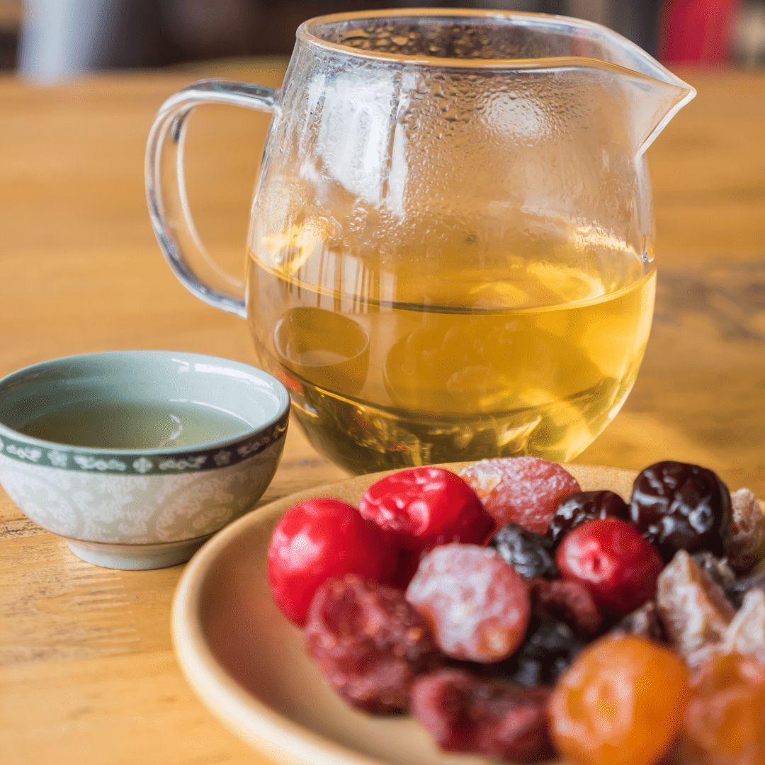 herbal tea with small asian teacup and saucer of fruit