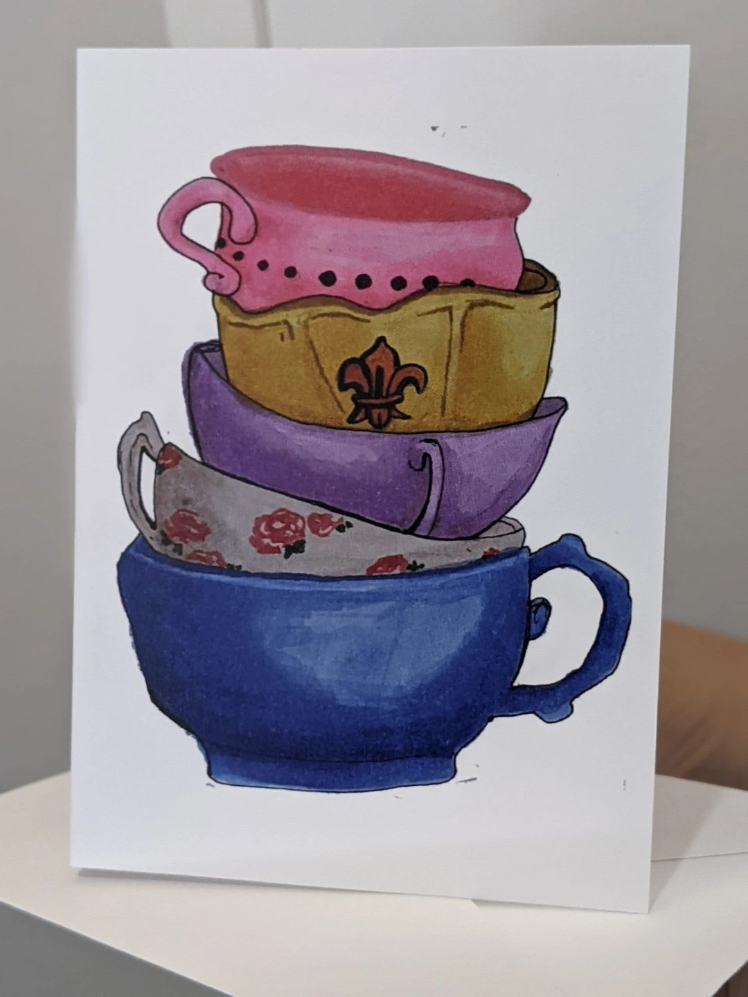 Card depicting stacked, colorful teacups. Illustration by the author, founder of the Tea Fairy Brigade.