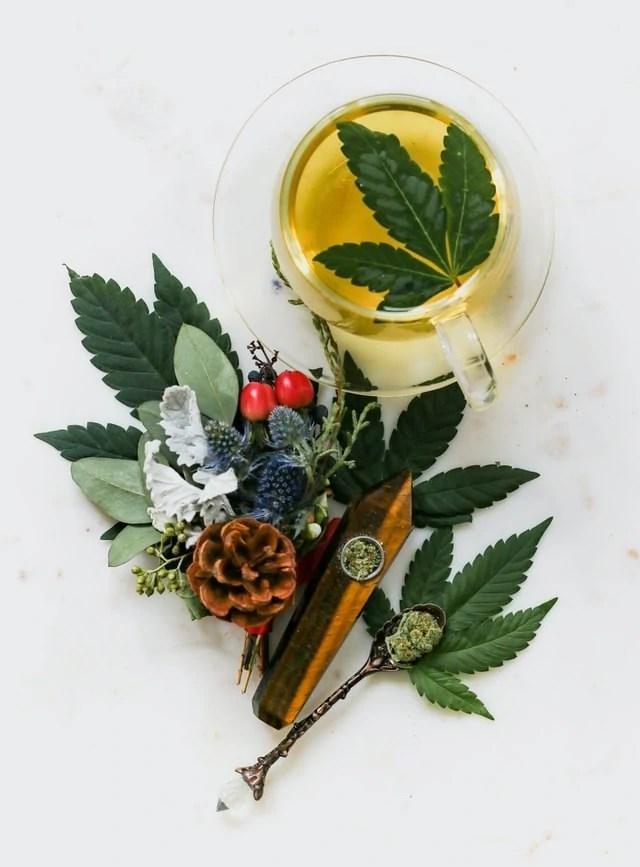 Hemp leaves, herbal tea, pinecones, and a tiger's eye crystal pipe