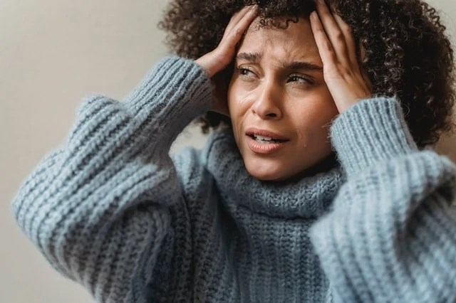 Black woman crying and holding her head