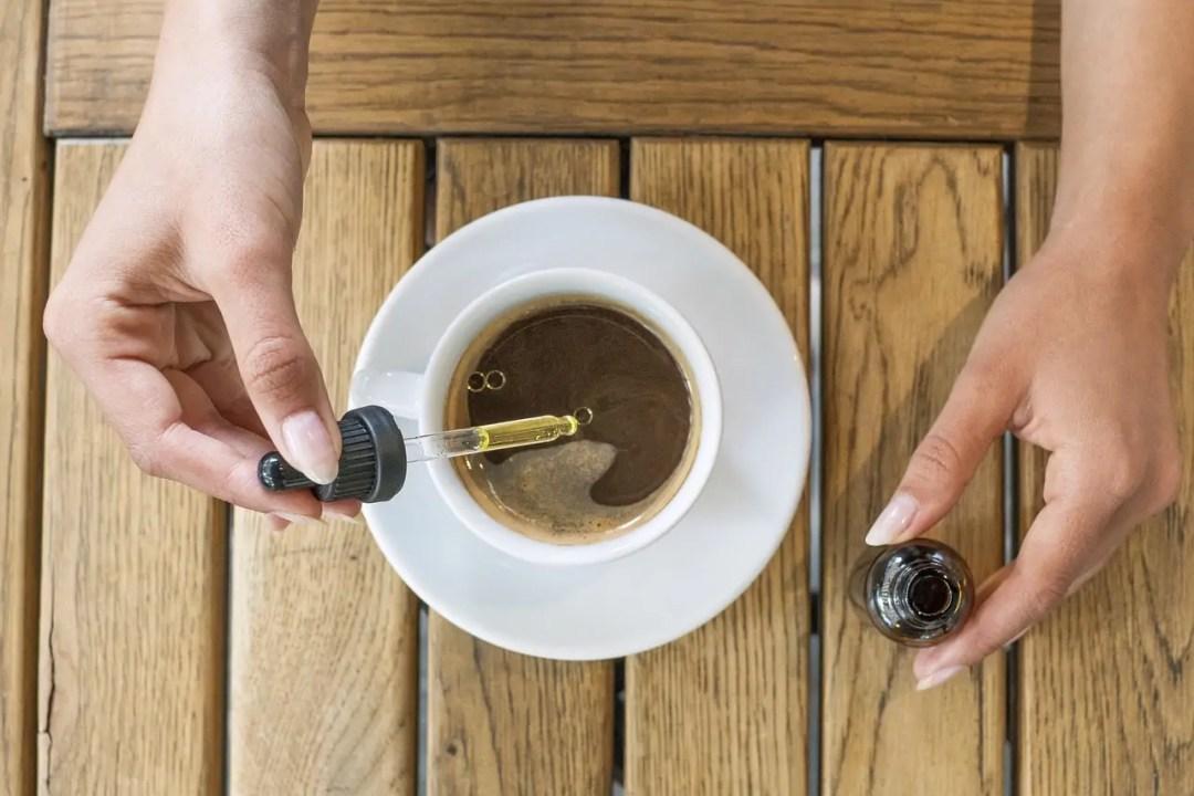 A dropper of CBD held above a tea cup