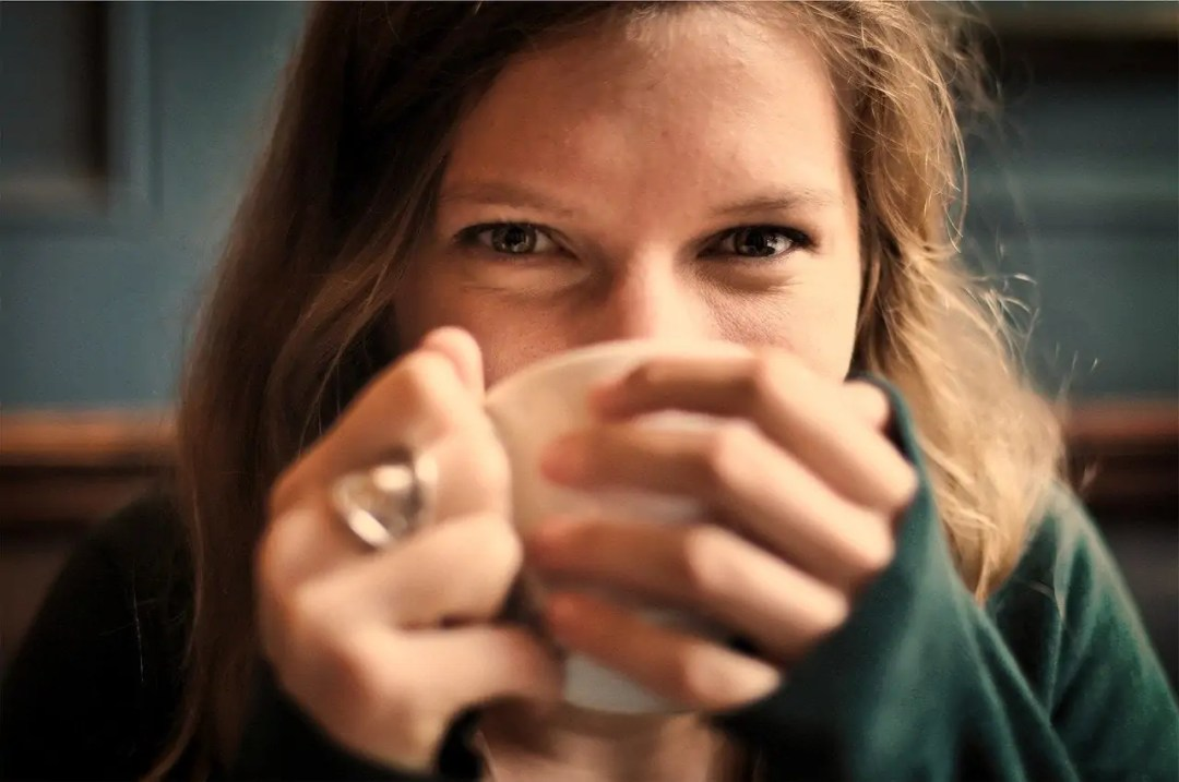 A woman holds a tea cup up to her face with both hands, eyes smiling