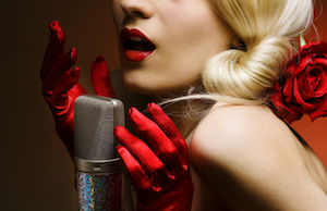 a hot blond with a rose in her hair with red satin gloves singing against red background