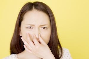 鼻をつまんでいる女性