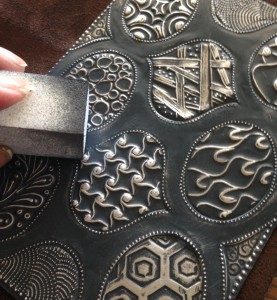 Once you have drew all the designs, remove the grey front color of the metal with a sanding block