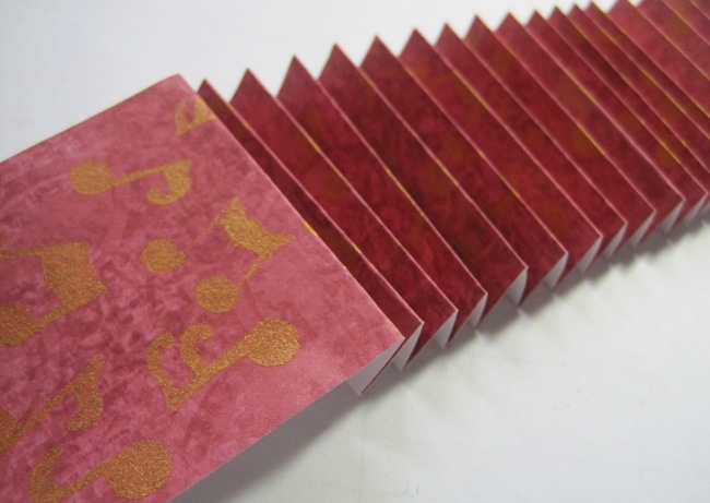 Accordion fold stenciled paper strip LEFKO