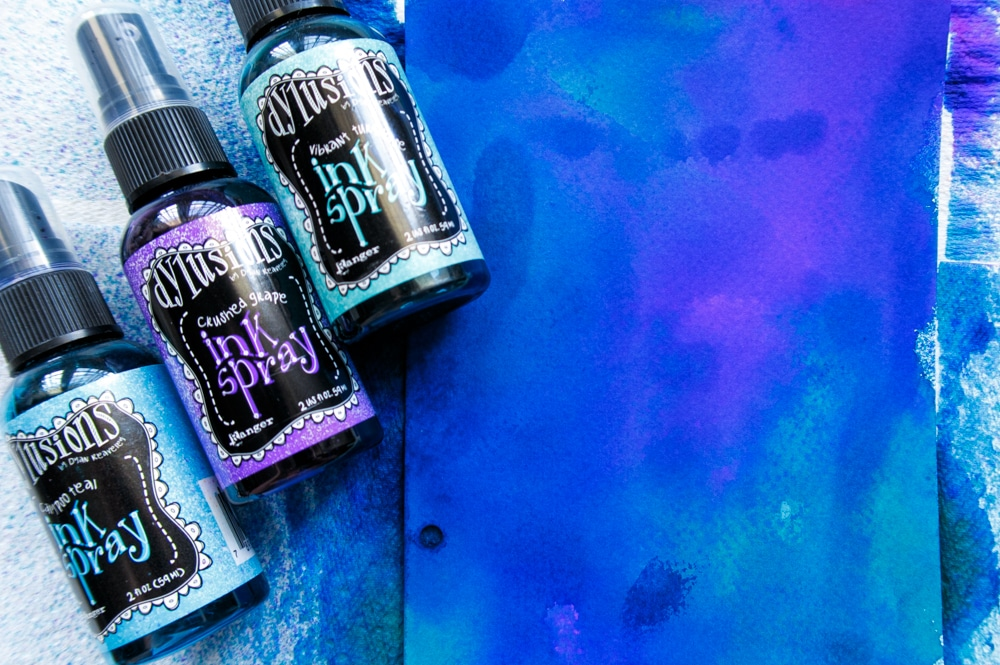 Creating a spray ink background using blue and purple Dylusions.