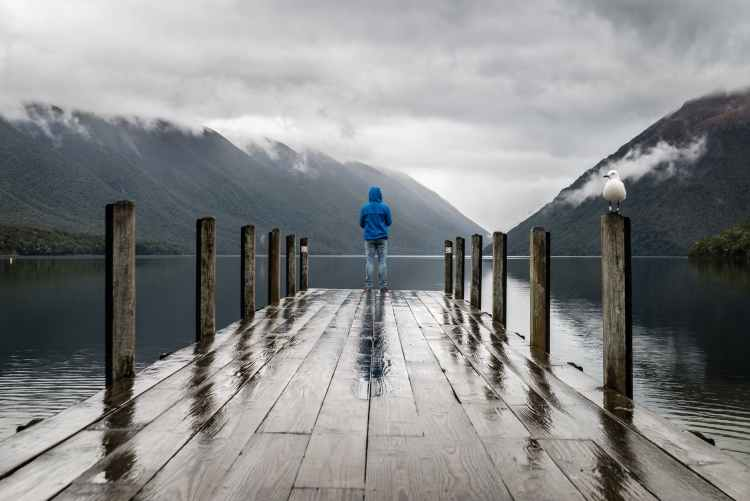 Man standing on the edge of a pier and reflecting