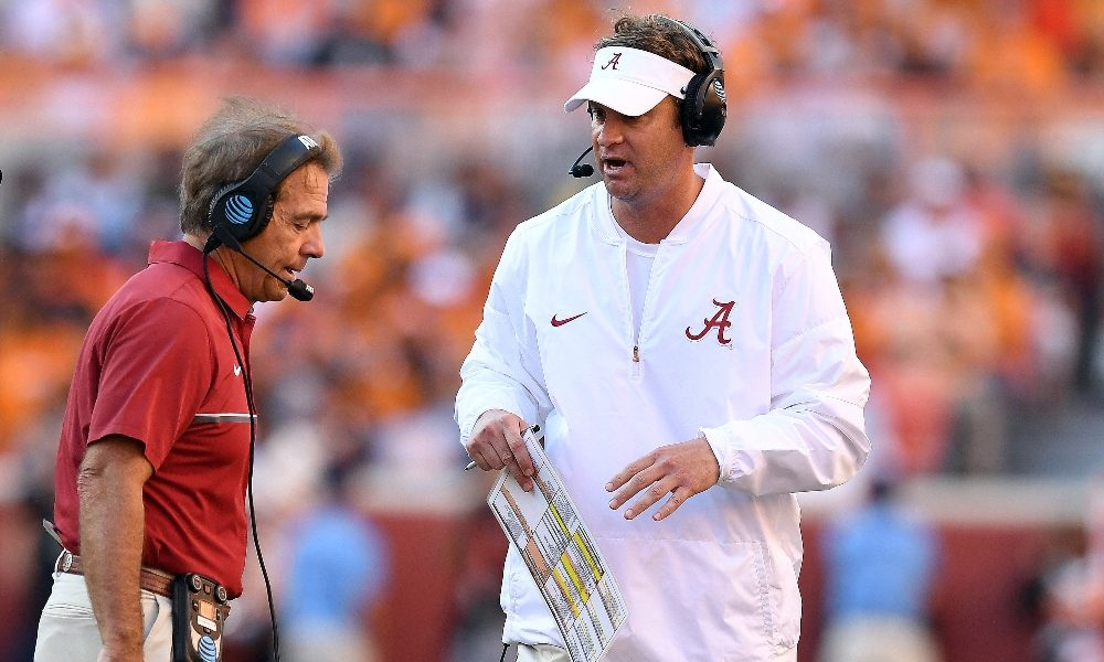 Lane Kiffin converses with Nick Saban on the sideline