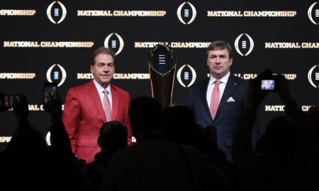 Nick Saban and Kirby Smart standing next to 2018 CFP Trophy in a presser